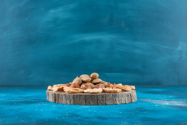 Nuts and dried fruits on a board on the blue surface