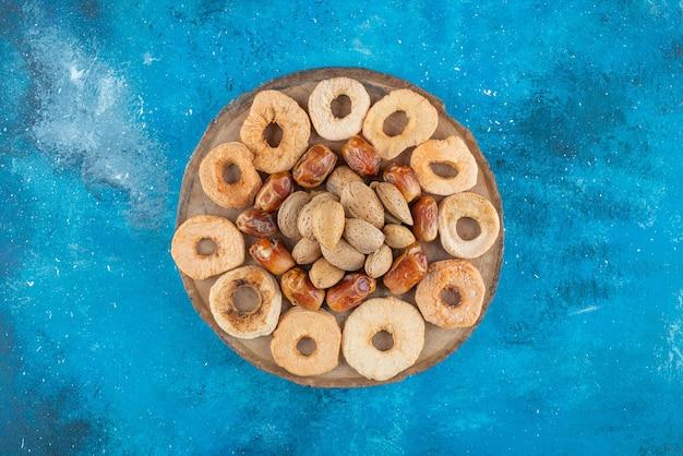 Noci e frutta secca su una tavola, sul tavolo blu.