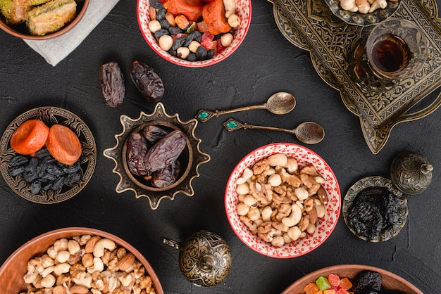 Nuts; dried fruits and dates on metallic; spoons and ceramic bowl on black background