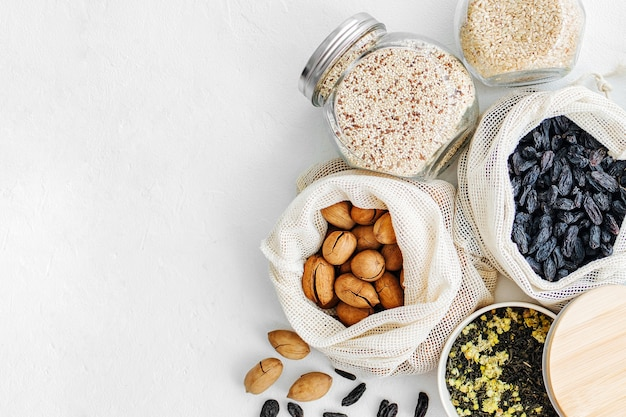 Nuts, dried fruits and  groats  in eco cotton bags and glass jars on white table in the kitchen. zero waste food shopping.  waste-free living