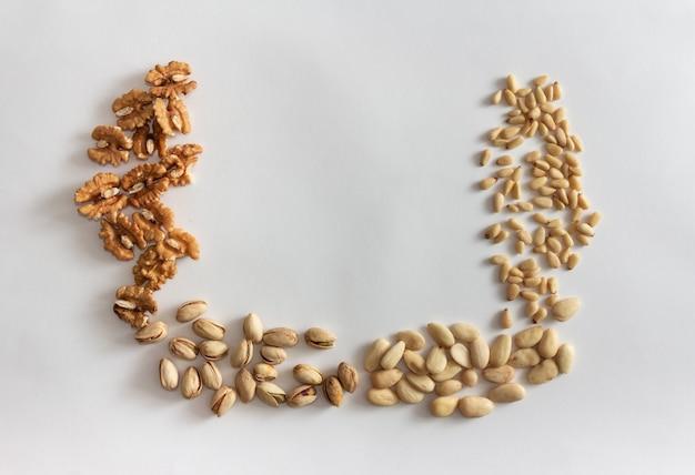 Рама орехов с грецкими орехами, арахисом, миндалем и кедровыми орехами на белом фоне. скопируйте пространство.