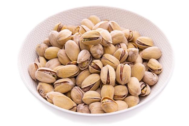 Орехи от фисташек в скорлупе до белой тарелки на белом фоне, изолированные предметы и продукты