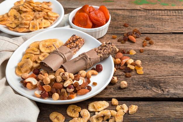 Орехи, батончики мюсли и сухофрукты в тарелках, на коричневом деревянном фоне.