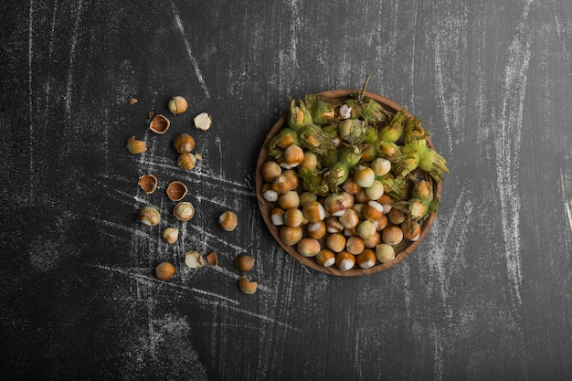 Nuts in green shells in a wooden platter and on the stone table in the middle