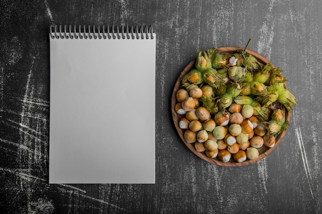 Nuts in green shells in a wooden platter with a notebook aside