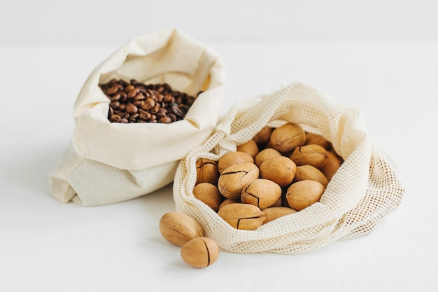 Nuts and  groats  in eco cotton bags  on white table in the kitchen. zero waste food shopping.  waste-free living