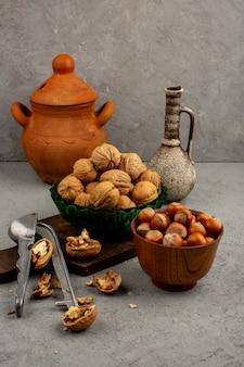 Nocciole e noci matte dentro il vaso rotondo marrone e il piatto verde circondati dalle brocche su un pavimento grigio