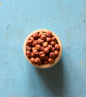 Nuts hazelnuts without shell in wooden saucer on the old blue wood