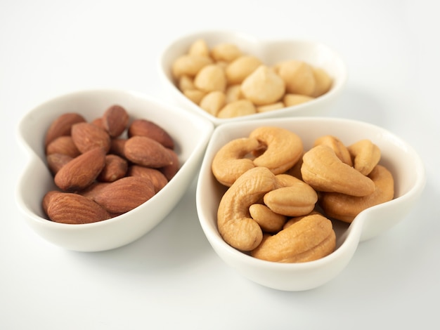 Nuts in heart shaped bowls isolated