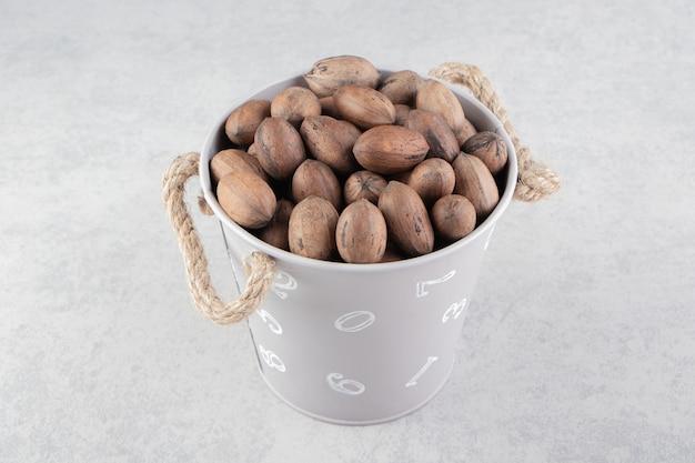 大理石の表面にある白いバケツのナッツ