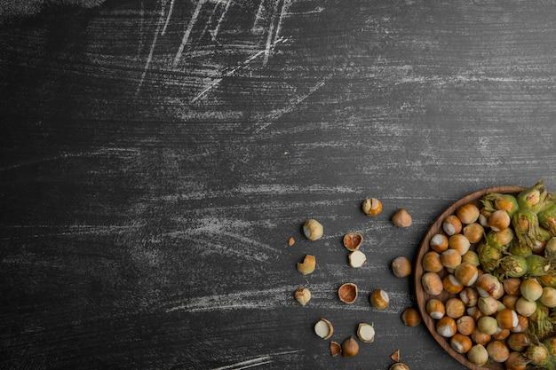Орехи в зеленой скорлупе на деревянном блюде и на каменном столе в нижнем углу