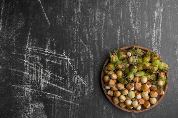 Орехи в зеленой скорлупе на деревянном блюде
