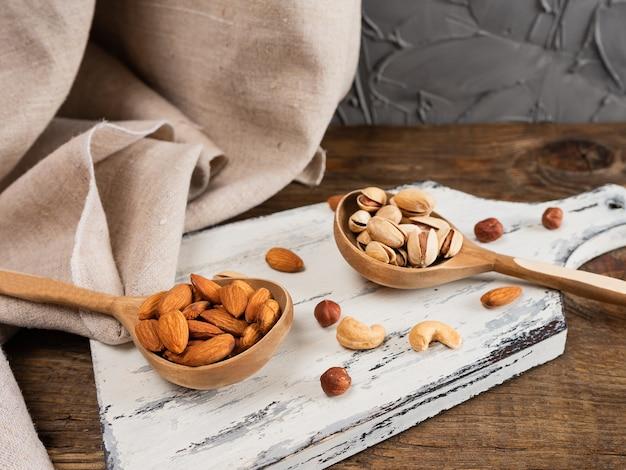 暗い木製のテーブルの上の木のスプーンのナッツ。