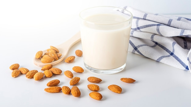Nuts milk and almonds in glasses with kitchen cloth on white table