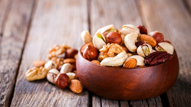 Nuts mixed in a wooden plate.