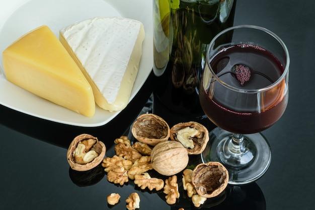 적포도주, 파마산 치즈, 브리 치즈 한 잔 옆에있는 견과류.