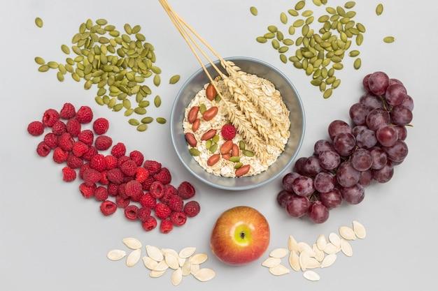 灰色のボウルにナッツ、オートミール、小麦の小穂。ラズベリーとブドウの房、テーブルの上のカボチャの種。フラットレイ。灰色の背景