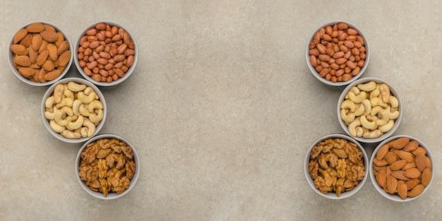 다른 품종의 견과류, 평면도. 혼합 견과류는 석조 조리대에 있는 그릇에 담겨 있습니다. 디자인 및 인쇄용. 텍스트, 레시피 또는 항목을 삽입할 위치입니다.