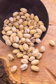 木の上の暗いカップから注がれた殻のピスタシアのナッツ
