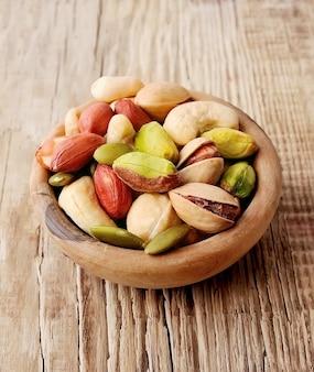 Орехи фистки, арахис, кешью на деревянной доске.