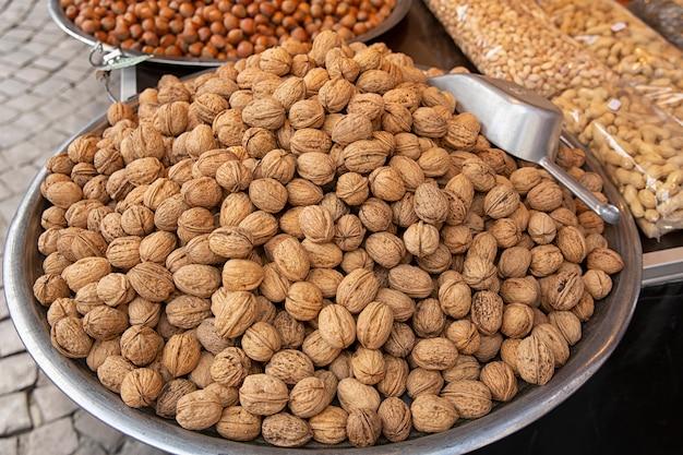 発売中の大皿のナッツ。東部のお菓子の市場。市場に出回っているさまざまなナッツの種類