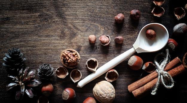 나무 테이블에 견과류입니다. 껍질과 껍질에 헤이즐넛. 갈색 테이블에 나무 숟가락과 견과류입니다.