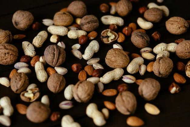 Гайки. фисташки, грецкий орех, фундук и арахис. смешанные орехи на черном фоне