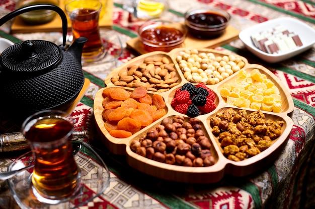 Орехи подают в бамбуковой тарелке в форме цветка с миндальным орехом, грецким орехом, курагой и сладостями