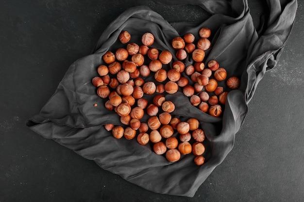 Орехи расстилают на черной скатерти, вид сверху.