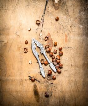 Орехи с щелкунчиком и скорлупой. на деревянном столе.
