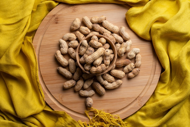 Nuts on the wooden bowl with yellow scarf