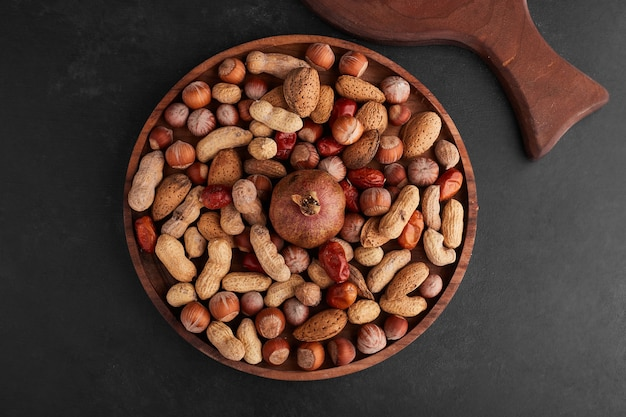 Nuts in a wooden platter in the center on black surface.