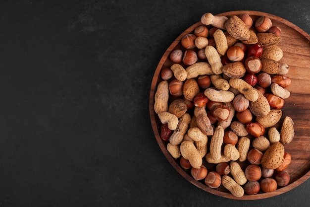 Nuts in a wooden platter, top view.