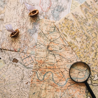 Nutshell boats and magnifying glass on maps