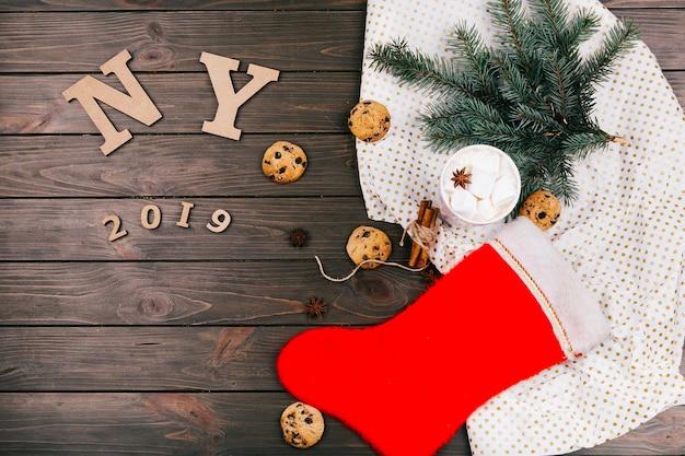 Деревянные буквы «ny 2018» лежат на полу, окруженные печеньем, еловыми ветками, горячим шоколадом и теплыми носками