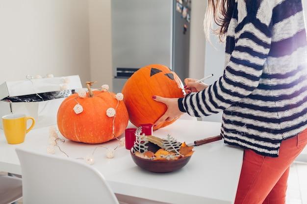 Молодая женщина делая джек-o-фонарик на хеллоуин на кухне. рисование глаз, носа и рта ручкой на тыкве