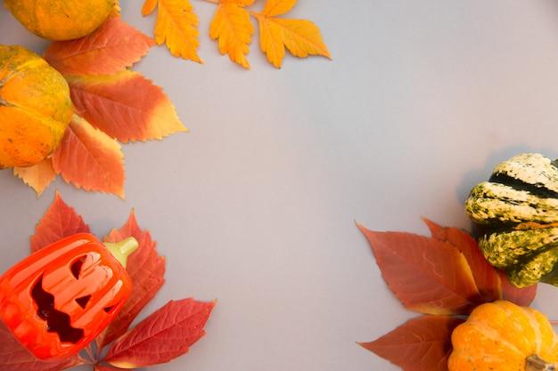 秋の組成物。カボチャ、怖いハロウィーン古いジャックoランタン、パステルグレーの背景の葉。