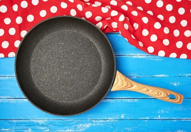 Пустая черная круглая антипригарная сковорода с ручкой o