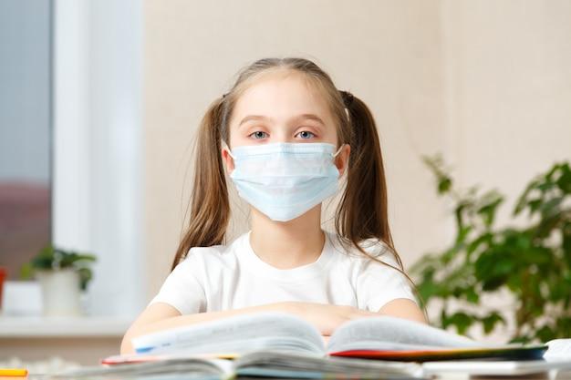 Дистанционное обучение онлайн-образование. школьница в медицинской маске делает домашнее задание o дома. карантин