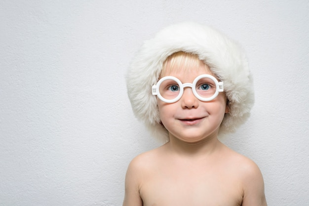 Маленький мальчик в очках и шапке санта-клауса стоит o