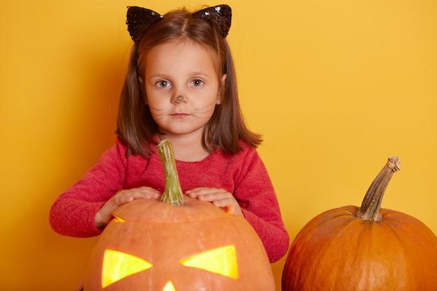愛らしい面白い白人少女の肖像画は、オレンジ色のハロウィーンのカボチャと赤いシャツを着ています。遊ぶ子供、秋の季節休暇のスタジオで楽しんでいます。パンプキンジャックoランタンに近いポーズの子供。