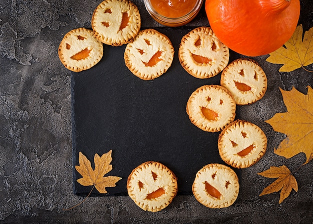 暗いテーブルの上のハロウィーンジャック-o-ランタンカボチャの形の自家製クッキー。上面図。