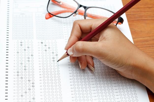 Рука женщин, держащих карандаш на стандартизованной тестовой форме с ответами, пузырьками и карандашом, фокус o