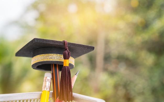 卒業した帽子バスケットにカラーの鉛筆をかけます。教育のための概念は成功研究oです