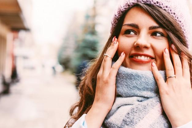 晩秋または冬のコートと帽子の若い美しい女性o