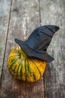 木製の背景に黒の魔女の帽子とジャックoランタンハロウィンのカボチャ。ハロウィーンパーティーのコンセプトです。ホリデーシーズンの挨拶、不気味な扱いのトリック。