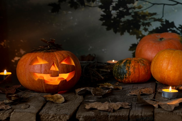 ハロウィーンカボチャヘッドジャックoランタンと夜の神秘的な森の木製テーブルの上のろうそく。ハロウィンデザイン