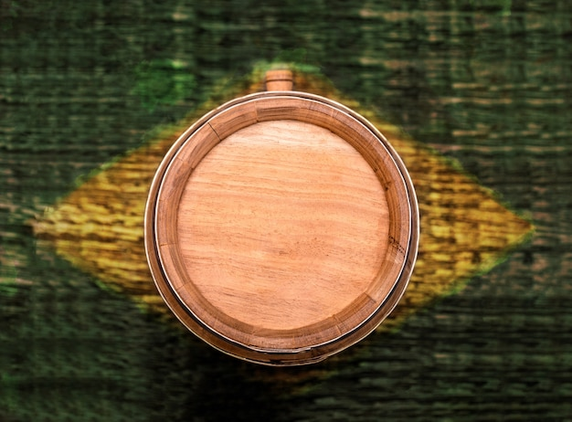 背景に黄色と緑のブラジル国旗の質感を持つオーク樽、「pinga」または「cachaã§a」飲料樽、ブラジルのカシャーサ建国記念日のコンセプト