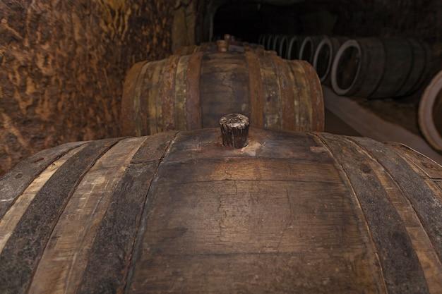 Дубовая пробка крупным планом, старый винный погреб с дубовыми бочками, бочки для вина в старых подвалах