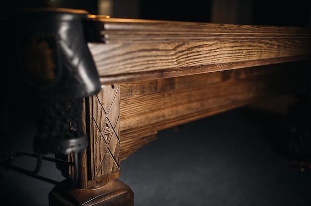 The oak decorative leg of a billiard table looks expensive